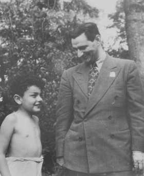 Joseph Schwartz, director of the American Jewish Joint Distribution Committee in Europe, speaks with a Jewish child survivor during a relief mission to Poland, July 22, 1946.