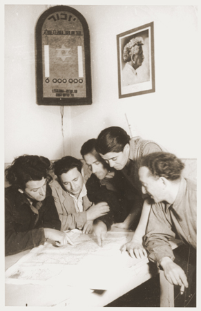 Members of Kibbutz Nili (a Zionist agricultural collective) study a map of Palestine. Above them hangs a wall plaque memorializing the six million Jews killed during the Holocaust. On the other wall is a photograph of the Labor Zionist leader, Berl Katznelson. Pleikershof, Germany, 1945-1948.