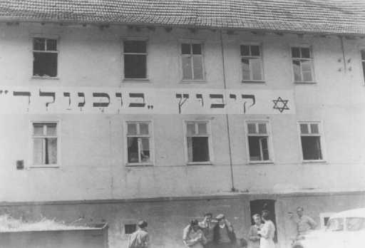 """Jewish refugees in front of the """"Kibbutz Buchenwald"""" building, where Jews received agricultural training in preparation for life in Palestine. Buchenwald displaced persons camp, Germany, ca. August 1946."""