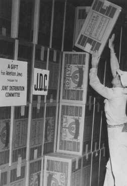 Boxes of matzah in a Joint Distribution Committee warehouse before distribution to Jewish survivors in displaced persons camps. Place uncertain, postwar.