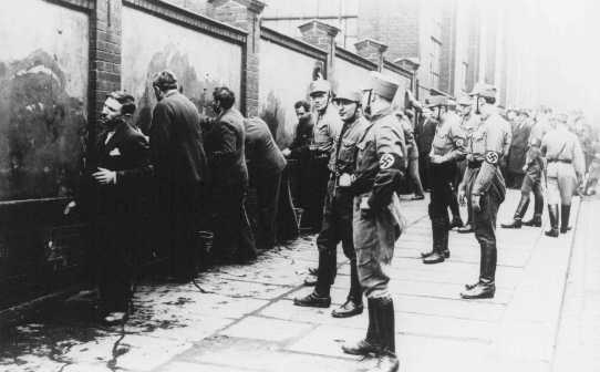 Political opponents of the Nazis, guarded by SA (Storm Troopers), are forced to scrub anti-Hitler slogans off a wall shortly after the Nazi assumption of power. Germany, March 1933.