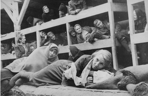 Women survivors huddled in a prisoner barracks shortly after Soviet forces liberated the Auschwitz camp. Auschwitz, Poland, 1945.