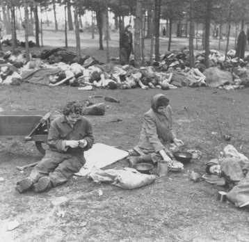 Soon after liberation, women camp survivors prepare food near piles of dead bodies. Bergen-Belsen, Germany, after April 15, 1945.