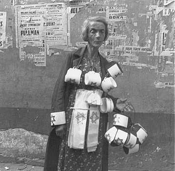Une femme décharnée vend des brassards frappés de l'étoile jaune dont le port était obligatoire pour les Juifs. A l'arrière plan, il y a des affiches de concerts ; presque toutes sont détruites. Ghetto de Varsovie, Pologne, 19 septembre 1941.