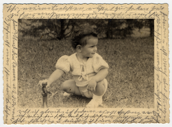 Photograph showing Margarida, Helen Reik's granddaughter, playing on a field in Teresopolis, Brazil, in April 1940. After her deportation to the Theresienstadt ghetto in Czechoslovakia, Helene yearned to record what was happening to her. This photograph was sent to Helene, who used it as paper for her diary in Theresienstadt. Helene's makeshift diary offers wistful memories of her husband and parents who died before the war, loving thoughts of her family who had left Europe in 1939, and a firsthand account of the illness and hospitalization that ultimately led to her death. Because resources were scarce in the Theresienstadt ghetto, Helene recorded her thoughts, recollections, and diary entries in the margins and on the backs of family pictures that she had brought with her, as well as postcards and letters she received while in the ghetto.