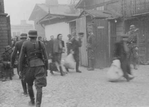 Au cours de la révolte du ghetto de Varsovie, des soldats allemands raflent des Juifs dans des usines pour les déporter. Ghetto de Varsovie, Pologne, avril ou mai 1943.