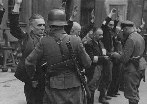 German soldiers arrest Jews during the Warsaw ghetto uprising. Poland, May 1943.