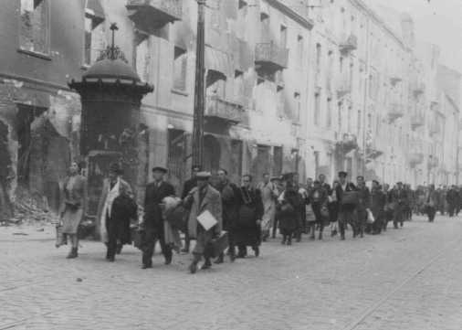 Jews rounded up during the Warsaw ghetto uprising are forced to march to the assembly point for deportation. Warsaw, Poland, April or May 1943.