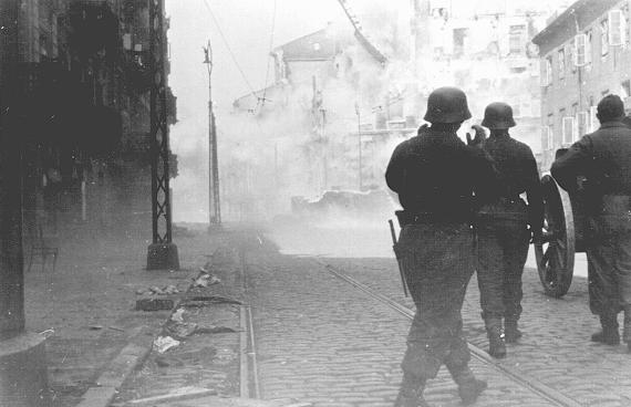 German soldiers direct artillery against a pocket of resistance during the Warsaw ghetto uprising. Warsaw, Poland, April 19-May 16, 1943.