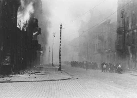 Photograph from SS General Juergen Stroop's report showing the Warsaw ghetto after the German suppression of the ghetto uprising. On the right, a column of Jews is transported out of the ghetto for deportation. Warsaw, Poland, April-May, 1943.