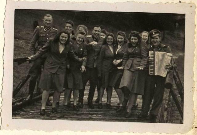 Las mujeres auxiliares de las SS (Helferinnen) bajan corriendo una rampa acompañadas por la música de un acordeonista.