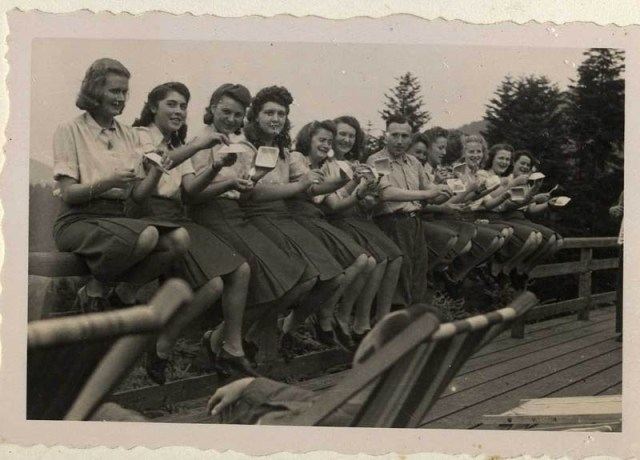 The SS female auxiliaries show with mock sadness that they have finished eating their blueberries, July 22, 1944.