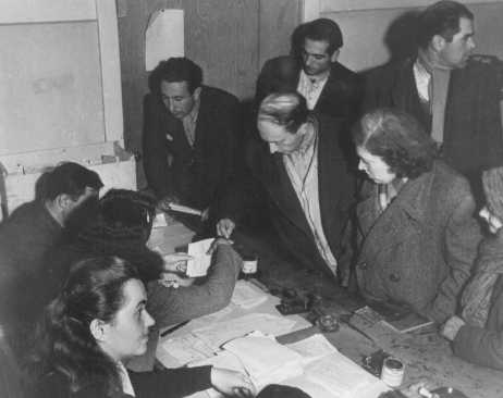 Checking identity cards of Jews who fled eastern Europe after the war (as part of the Brihah), in preparation for the journey to Palestine. Photograph taken by Henry Ries. Vienna, Austria, November 5-6, 1947.