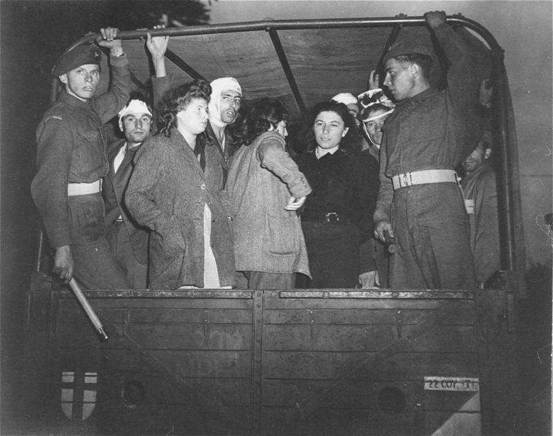 """Des soldats britanniques gardent des réfugiés juifs, débarqués de force de l' """"Exodus 1947,"""" dans des camions partant pour le camp de personnes déplacées de Poppendorf. Photo prise par Henry Ries. Kücknitz, Allemagne, 8 septembre 1947."""