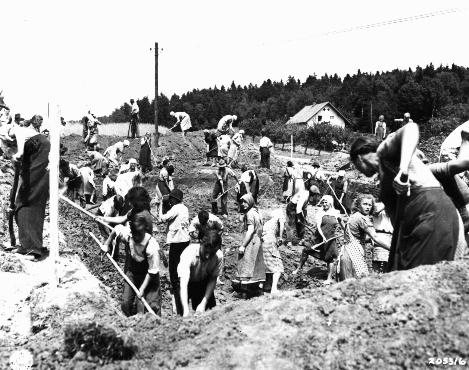 German civilians from the town of Nammering, under orders of American military authorities, dig graves for victims of a death march from the Buchenwald concentration camp. Germany, May 1945.