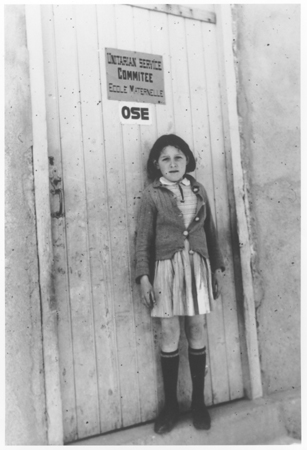 Lena-Helene Klizman (b. 1930) stands in front of the door to a nursery school in France sponsored by the Unitarian Service Committee and the OSE. This photograph was taken in Rivesaltes in 1942.