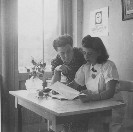 Margot Stein and Mrs. Zimmer, the wife of a physician of the Unitarian Service Committee, examine a document in their office at the Hotel Bompard internment camp. Margot Stein (later Samuel) was born in Germany and fled to France in 1933.  After being herself interned in Gurs, she was released through the efforts of OSE and served as a child-care and aide worker for the Unitarian Service Committee. Photograph taken in Marseilles, France, 1941-1942.
