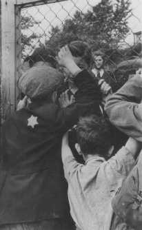 Jewish children say goodbye to parents through the fence of the Central Prison, the assembly point for deportations. Lodz ghetto, Poland, between 1942 and 1943.