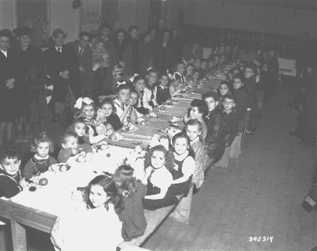 Fête de Hanoukka pour des enfants juifs au camp de personnes déplacées de Fürth. Les cadeaux étaient offerts par les familles des Américains résidant au poste militaire de Nuremberg. Allemagne, 9 décembre 1947.