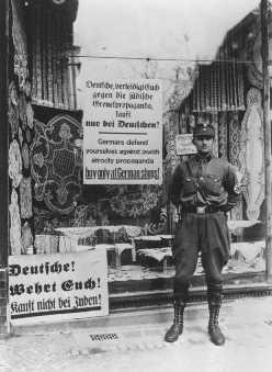خلال المقاطعة المعادية لليهود، يقف رجل SA خارج محل يملكه يهودي بعلامة  يطالب فيها الألمان ألا يشتروا من اليهود. برلين، ألمانيا، 1 أبريل 1933.