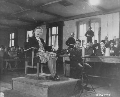 Ilse Koch testifies in her own defense at the trial of former camp personnel from the Buchenwald concentration camp. To her left is Herbert Rosenstock, an interpreter. July 8, 1947.