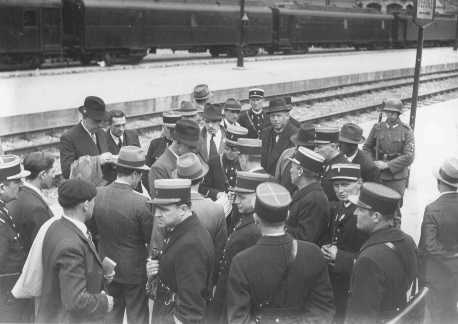 A group of Jewish men on a train platform with French policemen at the Austerlitz station before deportation to the Pithiviers internment camp. Paris, France, May 1941.