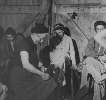 Soon after liberation, a British woman helps a camp survivor try on shoes. Bergen-Belsen, Germany, after May 1945.