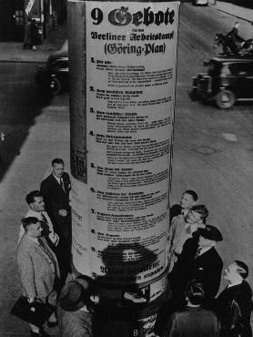 "German pedestrians read Hermann Goering's ""Nine Commandments for the Workers' Struggle,""  which included such exhortations as this one to German women: ""take hold of the frying pan, dust pan and broom and marry a man."" Berlin, Germany, May 1934."