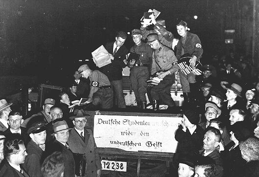 "Students and members of the SA unload books deemed ""un-German"" during the book burning in Berlin. The banner reads: ""German students march against the un-German spirit."" Berlin, Germany, May 10, 1933."