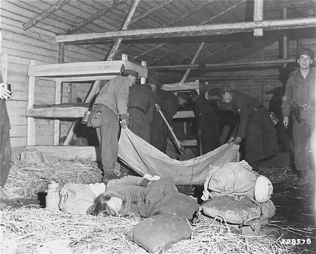 Medical corpsmen of the US 71st Infantry Division, 3rd US Army look on as captured German soldiers remove bodies from inside a barracks in Gunskirchen. In the foreground, a Jewish girl lies huddled in the straw on the floor of the barracks. Gunskirchen, Austria, May 7, 1945.