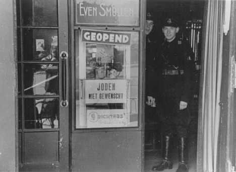 "Members of the paramilitary organization of the Dutch Nazi party stand in the doorway of a restaurant. The sign states ""Jews are not desired."" Amsterdam, the Netherlands, 1941-1942."