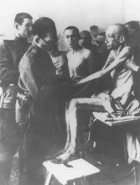 طبيب سوفيتي يفحص الناجين من محتشد أوشفيتز، بعد تحريره بقليل. بولندا، 18 شباط/فبراير، عام 1945.