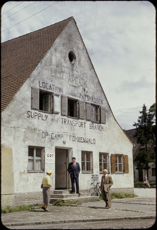 Exterior view of the ORT supply and transport building in the Foehrenwald displaced persons camp. This slide was taken by David Rosenstein during his inspection tour of the camp. After his return from the inspection tour in 1953, he briefed Congress on the plight of the remaining Jewish displaced persons in Europe and their inability to find permanent homes, nine years after the end of the war. Foehrenwald, Germany, 1953.