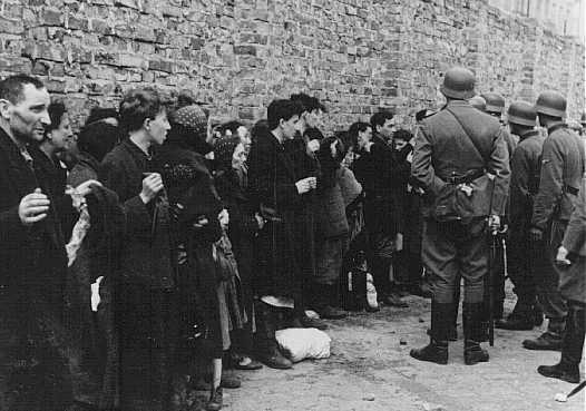 German soldiers interrogate Jews captured during the Warsaw ghetto uprising. Poland, May 1943.