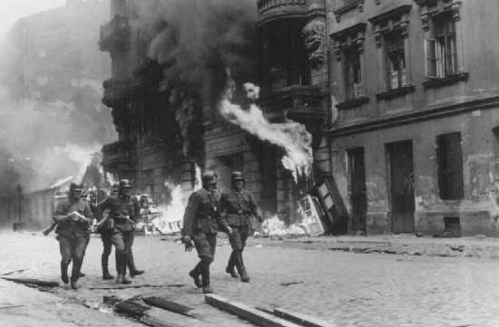German soldiers burn residential buildings to the ground, one by one, during the Warsaw ghetto uprising. Poland, April 19-May 16, 1943.