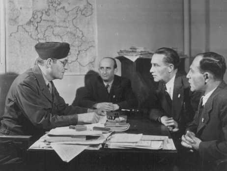 Members of the German Jewish community meet with David Wodlinger (left) of the Joint Distribution Committee. Bergen-Belsen displaced persons camp. Germany, after liberation, April 1945.