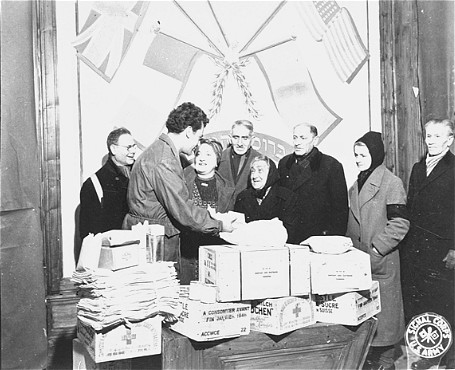 Harry Weinsaft, Joint Distribution Committee representative, gives aid packages to Jewish refugees. Vienna, Austria, postwar.