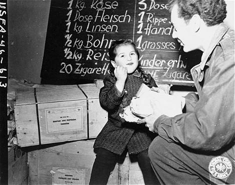 Harry Weinsaft du Joint (l'American Jewish Joint Distribution Committee, organisation caritative juive américaine - JDC) donne de la nourriture à un réfugié juif. Vienne, Autriche, après-guerre.