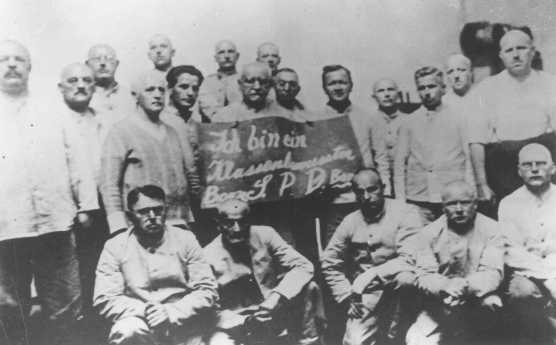 """Humiliation of prisoners: Social Democratic Party (SPD) inmates hold a placard which reads """"I am a class-conscious person, party boss/SPD/party boss."""" Dachau concentration camp, Germany, between 1933 and 1936."""