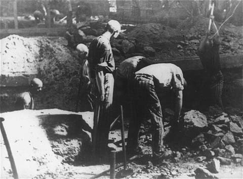 Prisoners at forced labor break stone with pickaxes in the quarry of the Flossenbürg concentration camp. Flossenbürg, Germany, date uncertain.