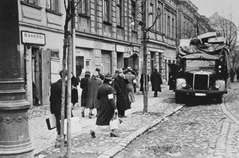 Residents of the Krakow ghetto walk past a German truck loaded with furniture confiscated from Jews. Krakow, Poland, ca. 1941.