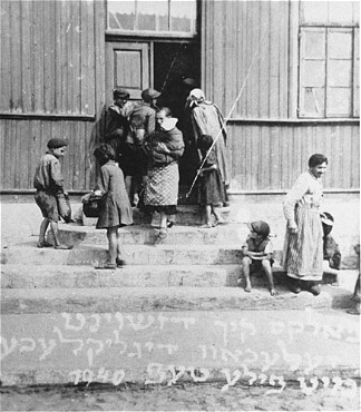 "Women and children at the door of a soup kitchen maintained by the American Jewish Joint Distribution Committee. The text in Yiddish reads ""The fortunate ones with full bowls."" Zelechow, Poland, 1940."