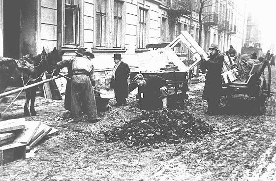 Juifs du ghetto de Cracovie déchargeant des meubles, devant être utilisés en tant que petit bois, à côté d'un tas de charbon. Cracovie, Pologne, vers 1941.
