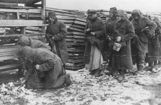 Soviet prisoners of war pause for rations during forced labor at the narrow-gauge railroad station. Mlawa, Poland, about 1943.