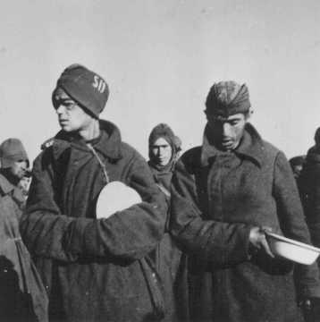 """Советские военнопленные, ожидающие раздачи пищи, в тюремном лагере """"Шталаг №8С"""". Более трех миллионов советских солдат, содержавшихся в германских лагерях и тюрьмах, погибли — главным образом, от недоедания и переохлаждения. Жагань, Польша, февраль 1942 года."""