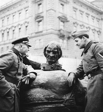 ポーランドの国の象徴を破壊するドイツ人。写真は、クラクフで横倒しにされたグルンバルトの記念碑の側に立つドイツ軍兵士。ポーランド、1940年。