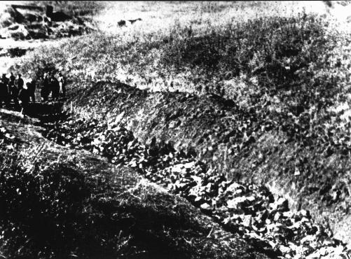 Soviet investigators (at left) view an opened grave at Babi Yar. Kiev, Soviet Union, 1944