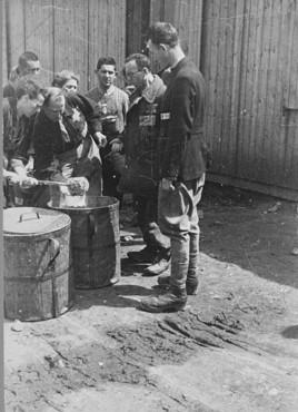Détenus au travail forcé rassemblés autour de conteneurs d'alimentation. Camp de travaux forcés de Plaszow , Pologne, 1943-1944.