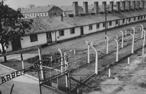 "View of the kitchen barracks, the electrified fence, and the gate at the main camp of Auschwitz (Auschwitz I). In the foreground is the sign ""Arbeit Macht Frei."" This photograph was taken after the liberation of the camp by Soviet forces. Auschwitz, Poland, 1945."