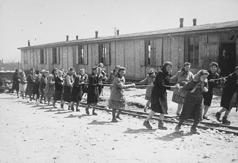 Women prisoners pull dumpcars filled with stones in the camp quarry. Plaszow camp, Poland, 1944.